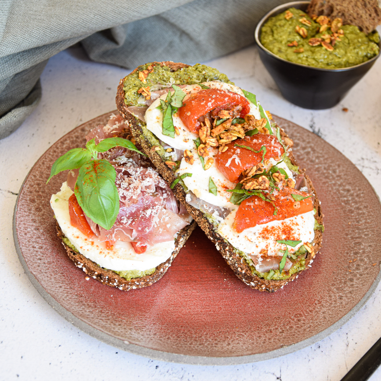 Toast with green pesto, mozzarella and prosciutto and XAVIES' Pure Toasted Nuts & Seeds